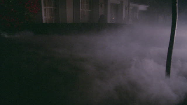 fog drifts through a suburban home's yard on a dark night. - nebbia video stock e b–roll