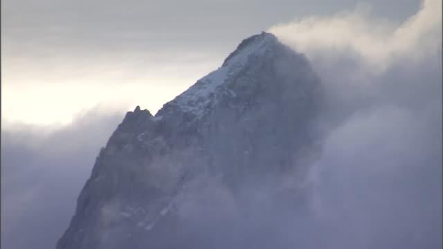fog enshrouds a mountain summit. - mountain peak stock videos & royalty-free footage