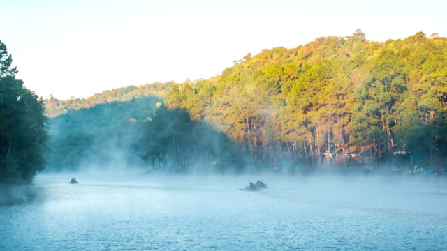 fog flowing on lake with people on bamboo boat at pang ung forestry plantations, mae hong son province, thailand - mae hong son province stock videos and b-roll footage