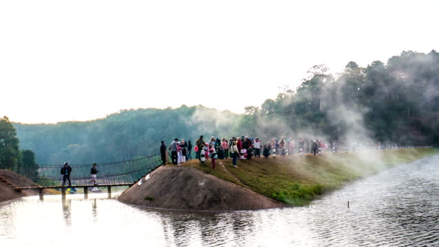 fog flowing on lake with people on dam at pang ung forestry plantations, mae hong son province, thailand - mae hong son province stock videos and b-roll footage