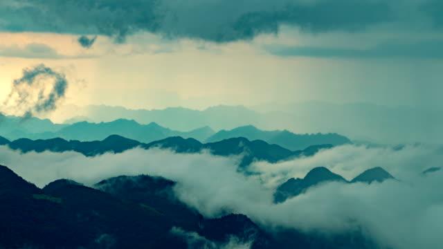vídeos de stock e filmes b-roll de fog flowing over mountains before rain - valley