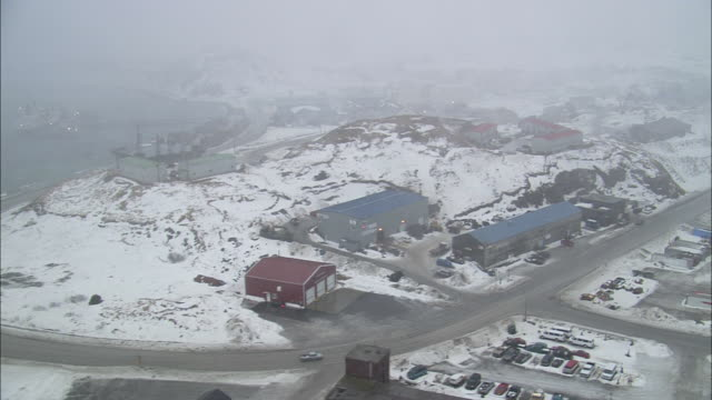 fog hovers over a snowy coastal town. - coastal feature stock videos & royalty-free footage