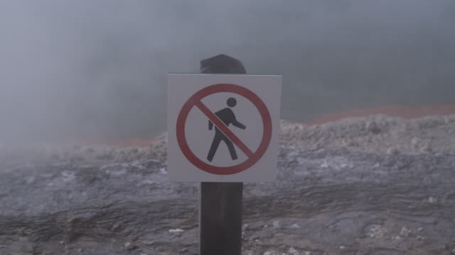 fog obscures a no walking sign by champagne pool at the waiotapu thermal area in rotorua, new zealand. - thermal pool stock videos & royalty-free footage