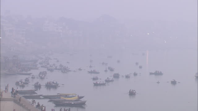 fog obscures rowboats that approach a river ghat in india. - flotilla stock videos & royalty-free footage