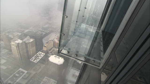 fog obscures the view from glass platforms attached high on the outside of chicago's willis tower. - sears tower stock-videos und b-roll-filmmaterial