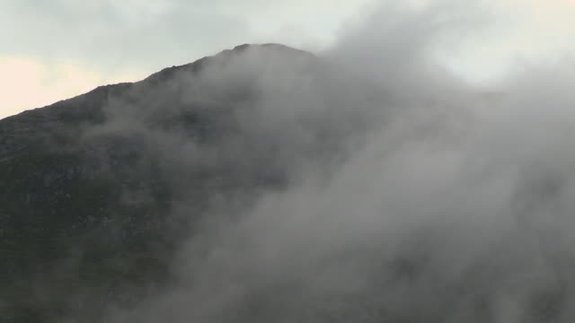 fog obscuring mountain peak - stability stock videos & royalty-free footage