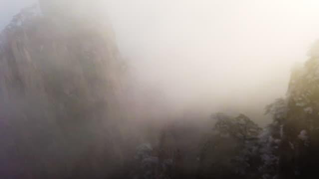vidéos et rushes de brouillard sur le pin givré de montagne de crête de montagne de montagne, huangshan, chine - culture chinoise