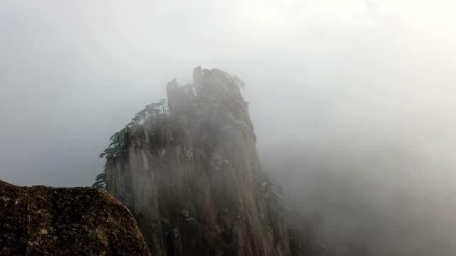 vidéos et rushes de brouillard sur mountain peak yellow mountain ou huangshan avec pin givré, huangshan, chine - unesco