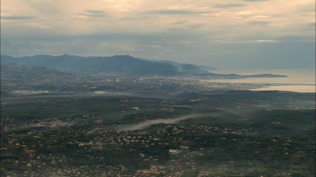 vídeos de stock, filmes e b-roll de aerial fog over green, hilly coastline with houses/ grasse, france - frança