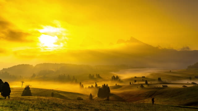ws time lapse fog over rolling landscape below majestic mountains at sunset,alpe di suisi, dolomites, italy - landscaped stock videos & royalty-free footage