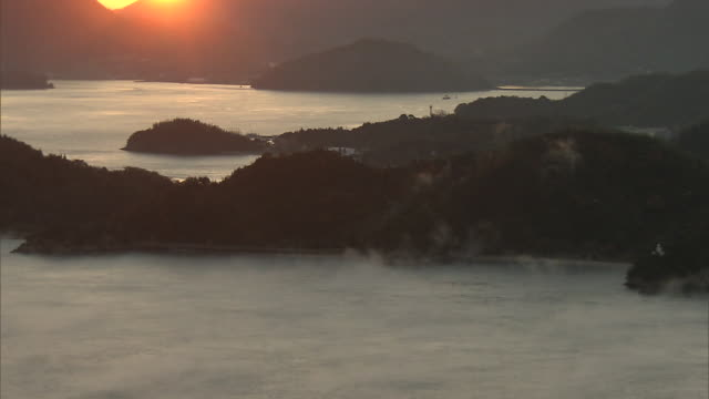 fog rising over the inland sea (setonaikai)  lit up by the morning sun - side lit stock videos & royalty-free footage