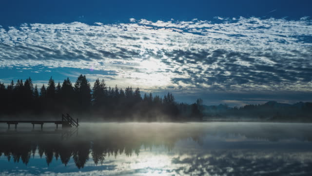 t/l fog rolling over lake kirchsee with sun covered by clouds - altocumulus stock videos and b-roll footage