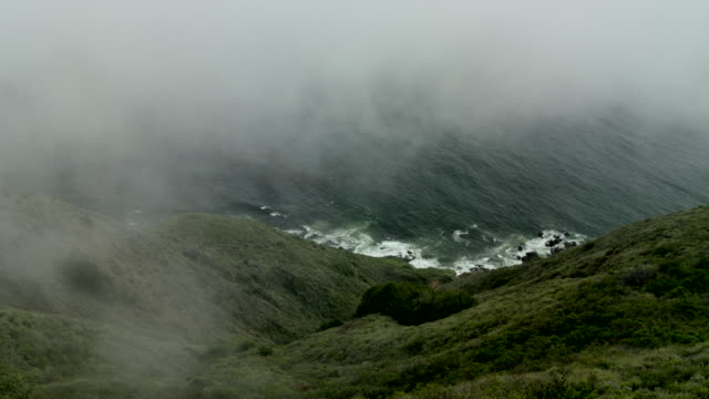 fog rolls over green hill overlooking big sur coastline - static - steep hill stock videos & royalty-free footage