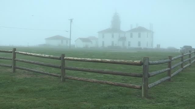 fog settles over the beavertail lighthouse in beavertail state park. - ローカルな名所点の映像素材/bロール