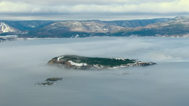 fog shrouds the coast of cape breton island and the surrounding waters. - oceano atlantico del nord video stock e b–roll