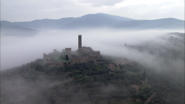 vídeos y material grabado en eventos de stock de fog surrounds a walled castle on a hilltop in central italy. - castillo estructura de edificio