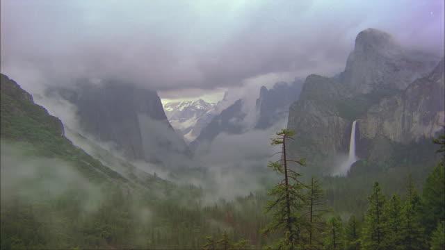 fog swirls around el capitan and bridalveil falls in yosemite national park. - bridal veil falls yosemite stock videos & royalty-free footage