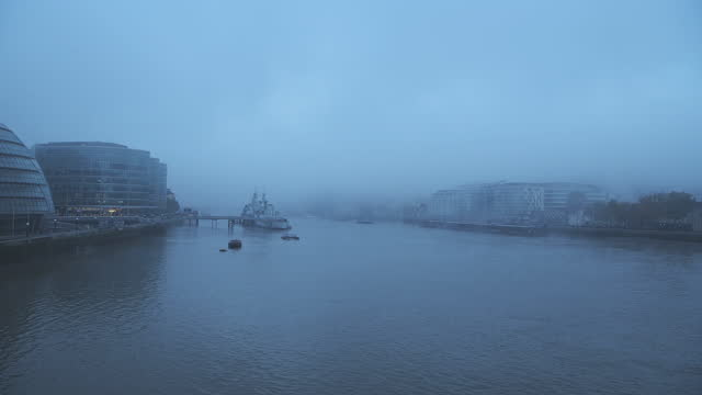 foggy and misty river thames in london on coronavirus covid-19 lockdown day one, in atmospheric weather with moody blue mist and fog around hms belfast and city hall by tower bridge, england, uk - british military stock videos & royalty-free footage
