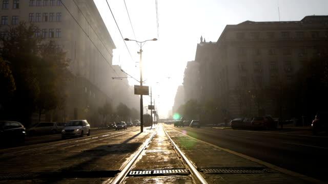 、早朝霧の街です。セルビアベオグラード街、ヨーロッパます。日の出を背景にし、車両と歩行者のシルエット - railway track点の映像素材/bロール