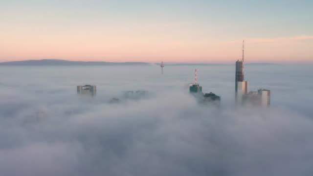 foggy morning in frankfurt - skyscrapers sticking out of the clouds - sideways - frankfurt main stock videos & royalty-free footage