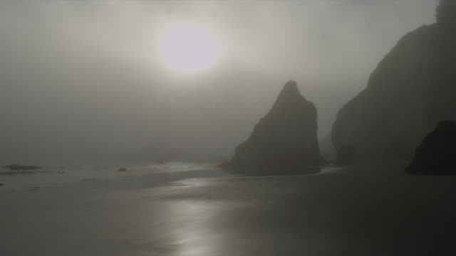 wide shot foggy silhouetted rock formations in ocean and on beach as surf washes up at sunset, oregon - surf rock stock videos & royalty-free footage