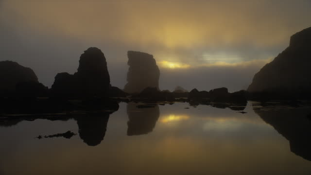 vídeos y material grabado en eventos de stock de wide shot foggy silhouetted rock formations on beach at sunset, oregon - vista marina