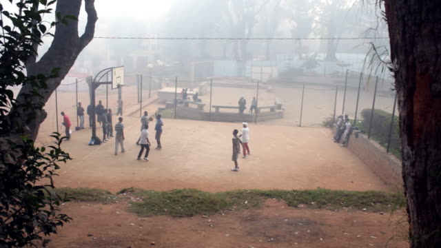 foggy view of young men playing basketball on a dirt court. - 2014 stock videos and b-roll footage