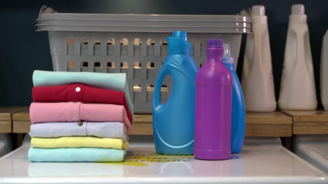 folded shirts on washing machine next to laundry products at a laundromat - laundry detergent stock videos & royalty-free footage