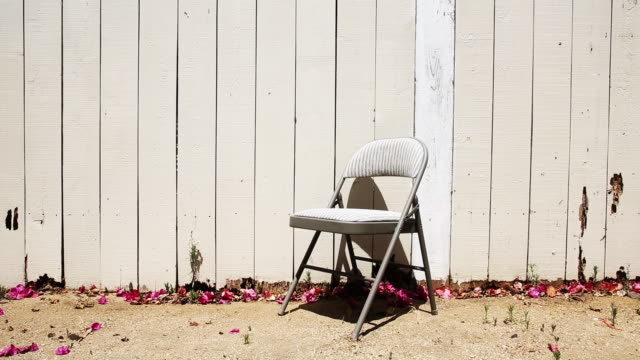 vídeos y material grabado en eventos de stock de folding chair in backyard by fence - silla plegable