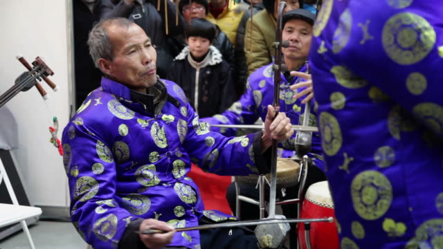 ms folk artists of chinese shadow play troupe playing  accompaniment with traditional music instrument during chinese spring festival audio / xi'an, shaanxi, china - folk music stock videos and b-roll footage
