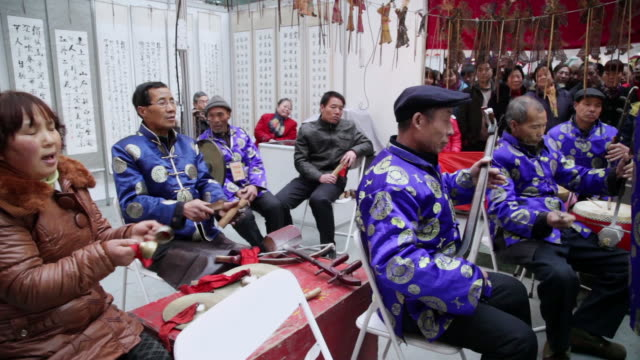ms pan folk artists of chinese shadow play troupe playing accompaniment with traditional music instrument during chinese spring festival  audio  / xi'an, shaanxi, china - folk music stock videos and b-roll footage