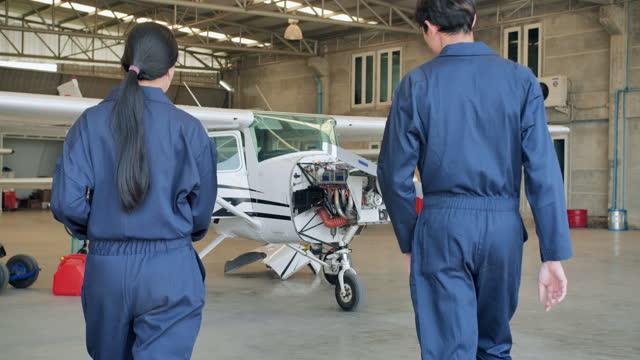 folgen sie der aufnahme zweier asiatischer ingenieure, die durch die flugzeugwartung gehen, während sie sprechen und lösungswartung im hangarflugzeug finden. frauen im mint-konzept. - luftfahrzeug stock-videos und b-roll-filmmaterial
