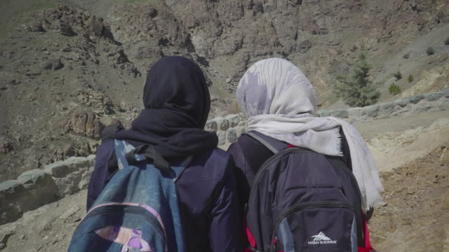 follow behind women hiking down mountain in hijabs - teheran video stock e b–roll