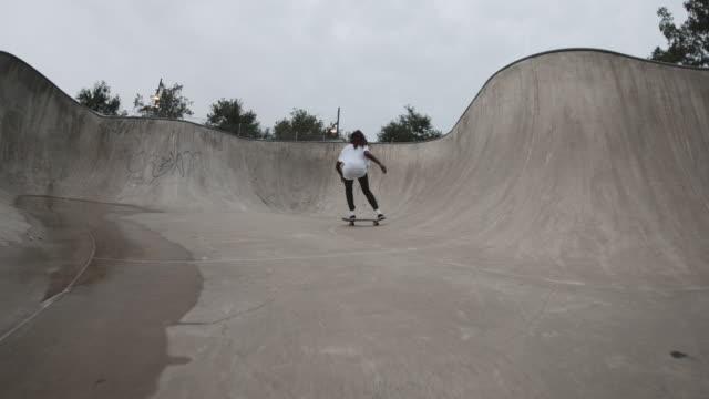 a follow cam of a gritty, black woman skateboarding through a skatepark bowl in 4k. - skateboard stock videos & royalty-free footage