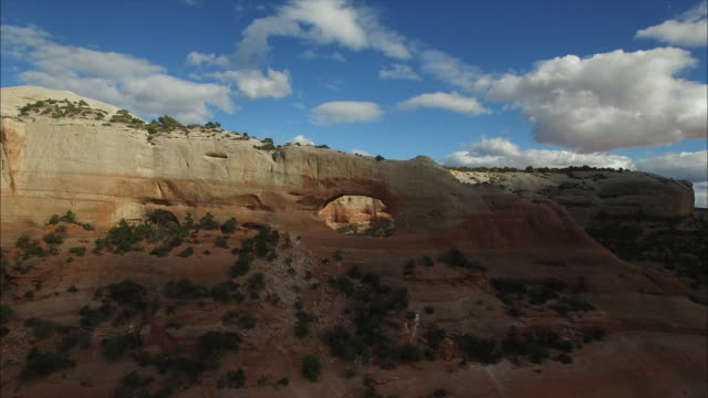 epic through arch follow clound cover amazing reveal - drone aerial video 4k arches national park, moab utah, corona arch, delicate arch, north window, turret arch, landscape arch, navajo arch in desert landscape, 4k cityscapes, landscapes & establishers - moab utah stock-videos und b-roll-filmmaterial