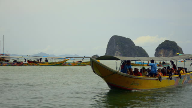follow : many passengers are on long boat - phang nga bay stock videos and b-roll footage