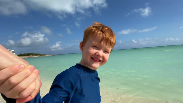 follow me concept - redhead boy holding his mother's hand on tropical beach in the caribbean - caribbean sea stock videos & royalty-free footage