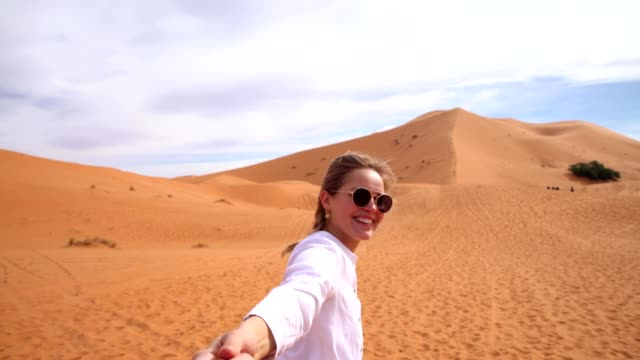 follow me concept. woman leading man desert dune. - following stock videos & royalty-free footage