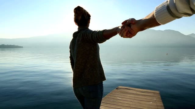 follow me concept-woman holding man's hand on lake pier, italy - piedmont italy stock videos & royalty-free footage