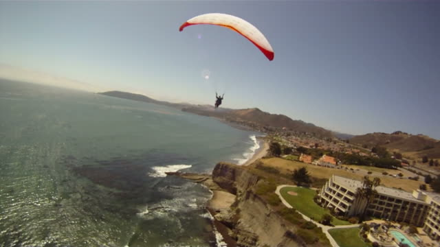 follow of paraglider as he sails over oceanfront cliffs - hang gliding stock videos and b-roll footage