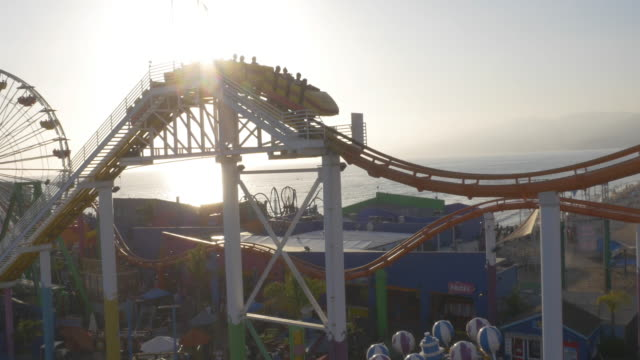 vidéos et rushes de follow roller coaster up and around, beach rollercoaster california, evening light, sun reflection, beach, coast, waves, people, reveal aerial, 4k, 13s, 3of3, stock video sale - drone - drone aerial view - parc d'attractions