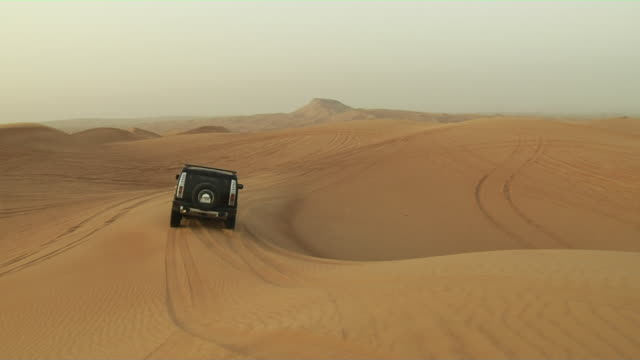 follow shot of car in desert dubai united arab emirates - 4x4 stock videos & royalty-free footage