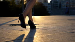 Follow to female legs in high heels shoes walking along city street in sunset time. Feet of business woman in high-heeled footwear going in the city. Girl stepping to work. Slow mo Close up Side view