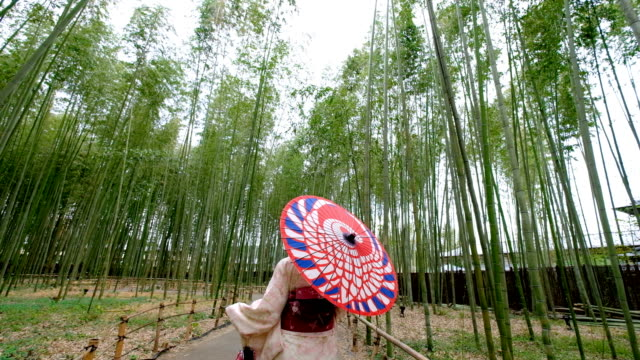 stockvideo's en b-roll-footage met 4 k follow-up shot: een aziatische vrouw draagt kimono jurk wandelen door bamboe bosjes shee en sagano. japanse cultuur - alleen één tienermeisje