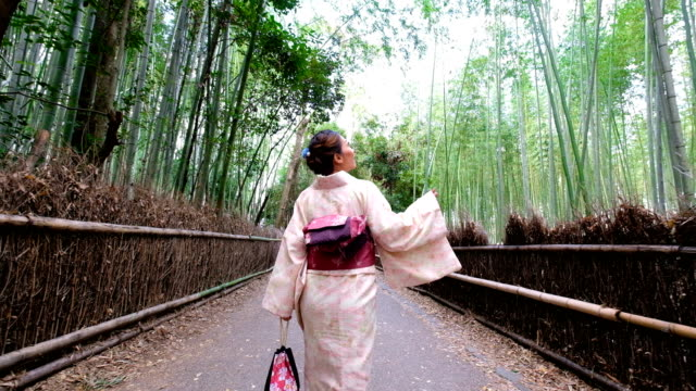 4k  follow up shot: a asian woman wearing kimono dress walking through bamboo groves arashiyama and sagano. japanese culture - giappone video stock e b–roll