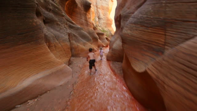 follow young hiker boy and young hiker girl down riverbed through canyon narrows - following moving activity stock videos & royalty-free footage