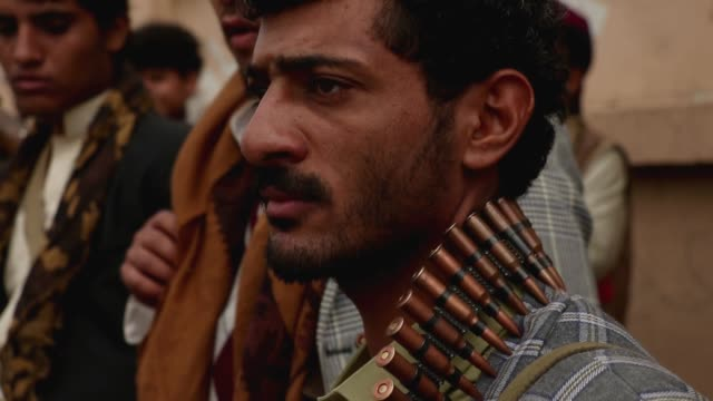 follower of the houthis group holds wears bullets around his neck as he takes part in a tribal gathering against the saudi-led coalition war on yemen... - 武器庫点の映像素材/bロール