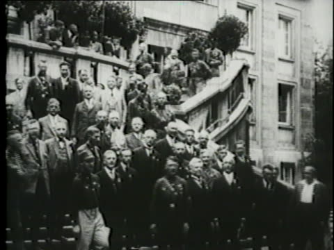 followers of hitler stand behind him on a grand staircase outside a government building. - 後を追う点の映像素材/bロール
