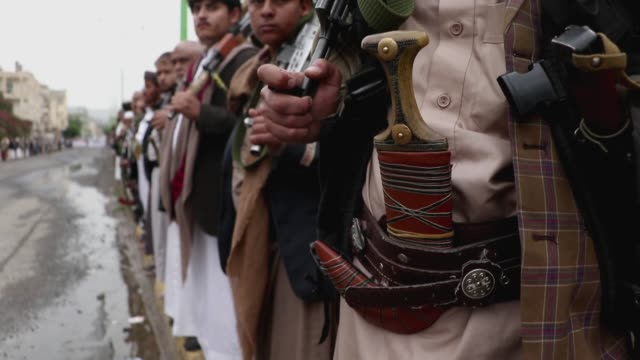 followers of the houthis group stand in line holding guns in a tribal gathering against the saudi-led coalition war on yemen on july 06, 2020 in... - 武器庫点の映像素材/bロール