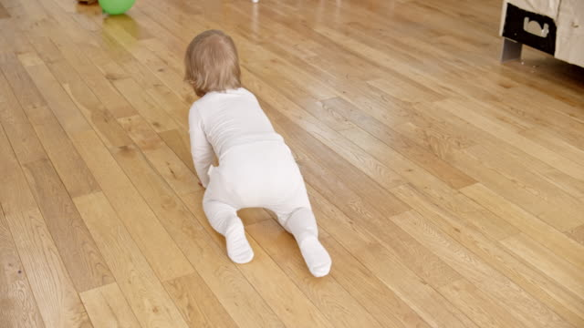 slo mo following a baby crawling across the floor - wooden floor stock videos & royalty-free footage